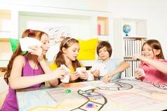 打与卡片的四个朋友桌面比赛 免版税图库摄影