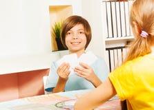 打与卡片的微笑的男孩比赛 免版税库存图片