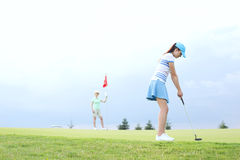 打与女性朋友的妇女高尔夫球反对天空 免版税库存照片