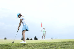 打与女性朋友的妇女高尔夫球反对天空 免版税库存图片