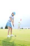 打与女性朋友的妇女高尔夫球拿着旗子反对天空 库存照片