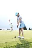 打与女性朋友的妇女高尔夫球拿着旗子反对天空 库存图片