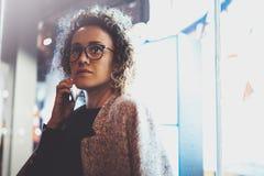 打与她的朋友的沉思俏丽的妇女交谈电话通过手机,当站立在晚上在街道时 免版税库存照片
