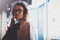 打与她的朋友的沉思俏丽的妇女交谈电话通过手机,当站立在晚上在街道时 免版税库存图片