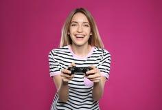 打与控制器的情感年轻女人电子游戏 免版税库存照片