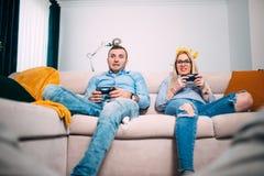 打与控制杆控制器的朋友电子游戏 获得与现代技术的乐趣和使用在控制台的青年人 免版税库存照片
