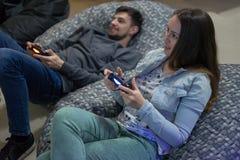 打与控制杆的愉快的夫妇朋友电子游戏坐辎重袋椅子 库存照片