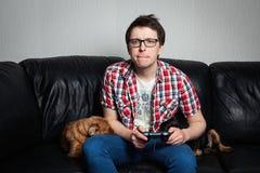 打与控制杆的红色衬衣和玻璃的年轻人电子游戏坐有两条狗的一个黑皮革长沙发 他 图库摄影