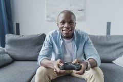打与控制杆的非裔美国人的人电子游戏 免版税库存图片