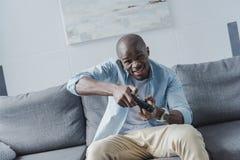 打与控制杆的非裔美国人的人电子游戏 免版税库存照片