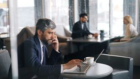 打与智能手机的打电话和使用膝上型计算机的中年人在咖啡馆 股票录像