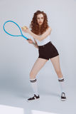 打与球拍和球的美丽的年轻行家女孩网球 库存照片
