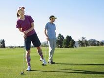 打与男性朋友的妇女高尔夫球 免版税图库摄影