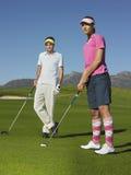 打与男性朋友的妇女高尔夫球 图库摄影
