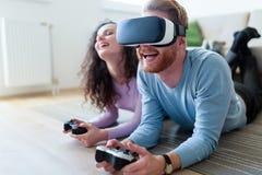 打与虚拟现实耳机的年轻夫妇比赛 免版税库存照片