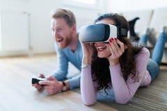 打与虚拟现实耳机的年轻夫妇比赛 免版税库存图片