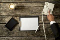 打与他的办公室t的买卖人顶视图一个电话 免版税库存图片