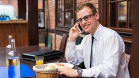 打与他的智能手机的微笑的年轻商人一次电话在餐馆。 图库摄影