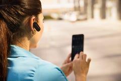 打与bluetooth设备的女商人一个电话 免版税图库摄影