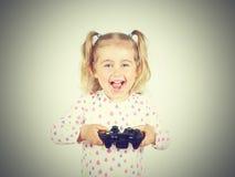 打与gamepad的小女孩电子游戏在手上 库存图片