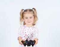 打与gamepad的小女孩电子游戏在手上 免版税库存图片