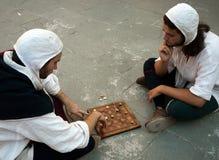 打中世纪棋的服装的二个人 免版税库存照片