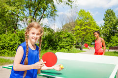 打乒乓球的两个愉快的女孩外面 免版税库存图片