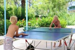 打乒乓球的两个愉快的男孩户外 免版税库存照片