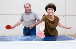 打乒乓球的愉快的成熟spousesn 库存图片