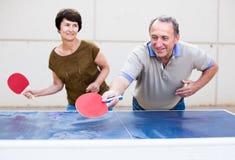 打乒乓球的愉快的成熟spousesn 免版税图库摄影