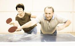 打乒乓球的成熟夫妇 免版税库存照片