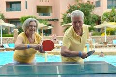 打乒乓球的年长夫妇 免版税库存照片