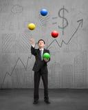 打五颜六色的球的常设商人 免版税库存照片