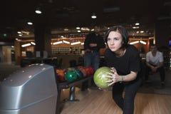 打保龄球的美丽的女孩 有球的妇女滚保龄球的在行动的手上 免版税库存照片