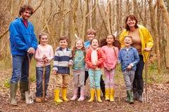 打冒险比赛的成人和孩子在森林里 免版税库存照片