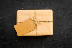 打包包装的箱子包裹与与空的标签大模型的工艺纸在黑背景顶视图拷贝空间 免版税图库摄影