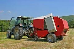 打包机圆的干草拖拉机 免版税库存图片