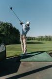 打单独高尔夫球的时髦的人在高尔夫球场 库存图片