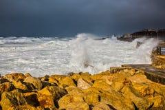 打反对岸的巨大的起泡沫的波浪 库存照片