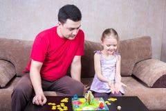 打台式游戏机的爸爸和女儿 免版税库存图片
