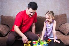 打台式游戏机的爸爸和女儿 库存照片