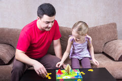 打台式游戏机的爸爸和女儿 库存图片