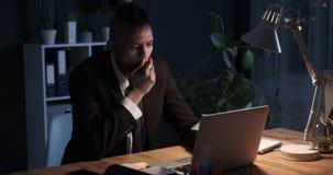 打呵欠和使用膝上型计算机的商人在夜办公室 股票录像