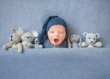 打呵欠和放在长毛绒玩具之间的新出生的男婴 免版税库存图片
