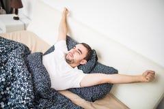 打呵欠和舒展在家醒来在床上的人 免版税图库摄影