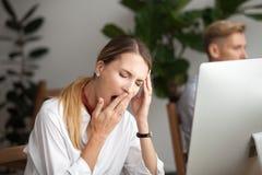 打呵欠在工作场所感觉缺乏的乏味疲乏的女实业家s 免版税库存图片