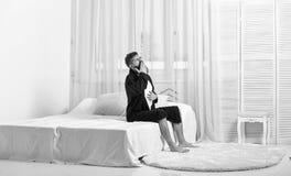 打呵欠在早晨的困面孔的人 唤醒概念 长袍的人坐床,在背景的白色帷幕 强壮男子 免版税库存照片