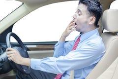 打呵欠在汽车的年轻人 免版税库存照片