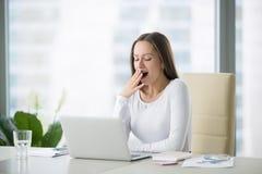 打呵欠在膝上型计算机附近的少妇 免版税库存照片