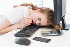 打呵欠在键盘的睡着的女实业家在办公室 免版税图库摄影